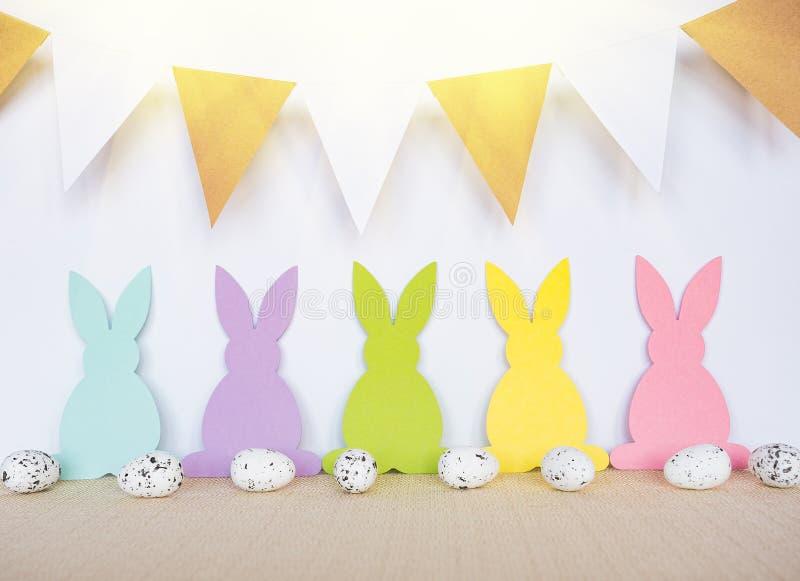 Påskbakgrund med ägg, kaniner och girlandflaggor royaltyfri foto