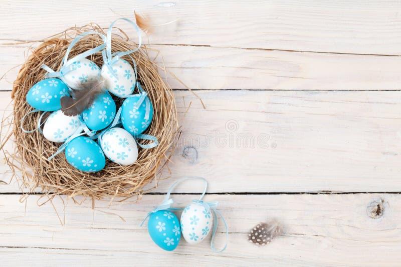 Påskbakgrund med blåa och vita ägg i rede arkivfoto