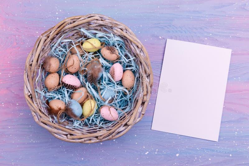 Påskbakgrund med färgrika vaktelägg, fjädrar i en vide- korg och ett tomt pappers- near det, bästa sikt kopiera avstånd royaltyfri foto