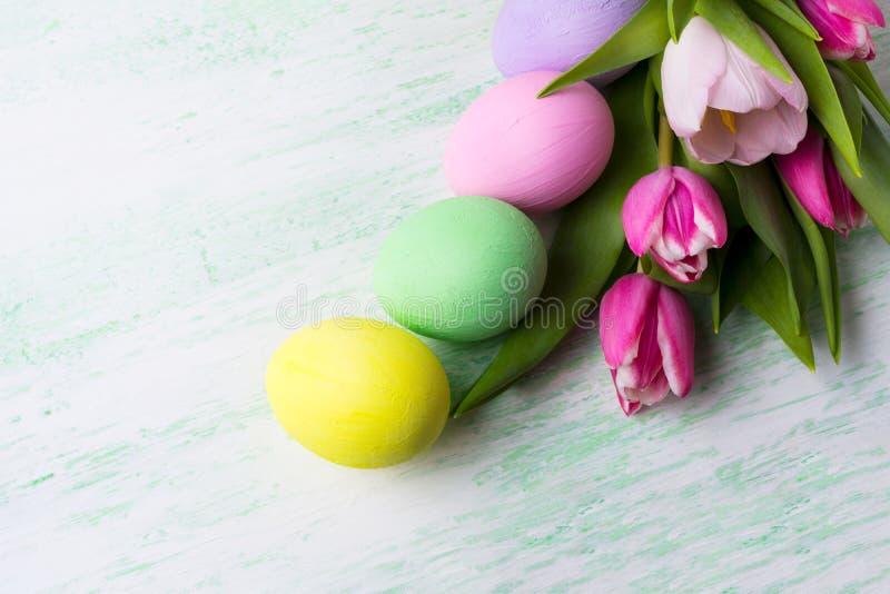 Påskbakgrund med lilor, rosa färger, gräsplan, gulnar målade ägg royaltyfri fotografi