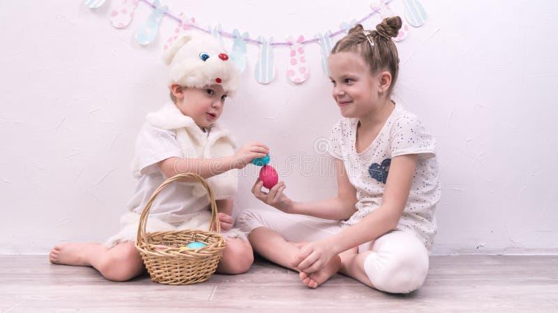 Påskberöm: En pojke klädde som en påskkaninflicka med påskägg arkivbild