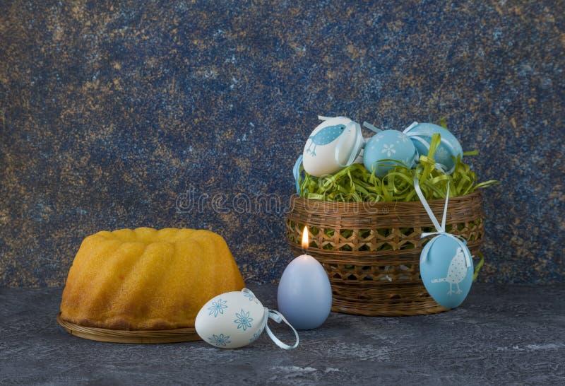 Påskbröd och blåa påskägg i en korg på mörkerstentabellen arkivbild