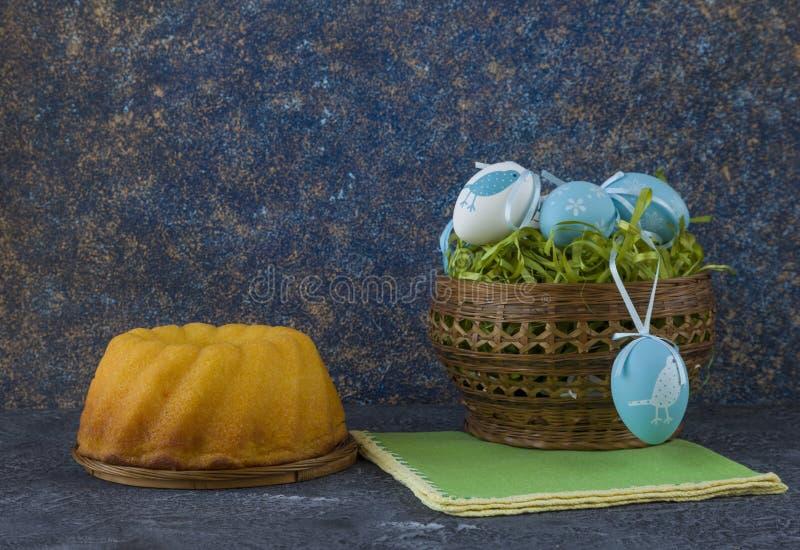 Påskbröd och blåa påskägg i en korg på mörkerstentabellen arkivfoton