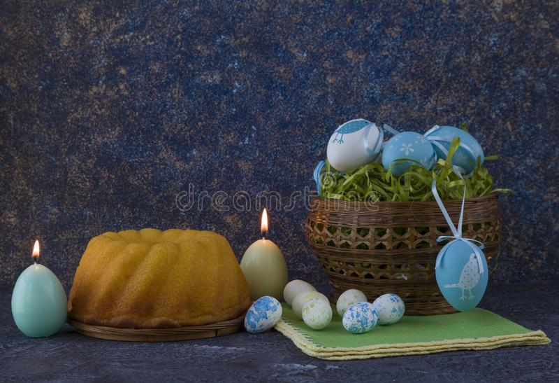 Påskbröd och blåa påskägg i en korg på mörkerstentabellen arkivfoto