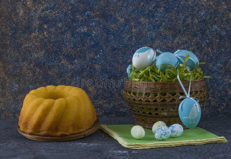 Påskbröd och blåa påskägg i en korg på mörkerstentabellen royaltyfri foto