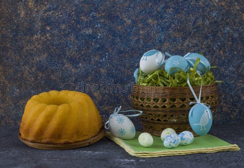 Påskbröd och blåa påskägg i en korg på mörkerstentabellen arkivbilder