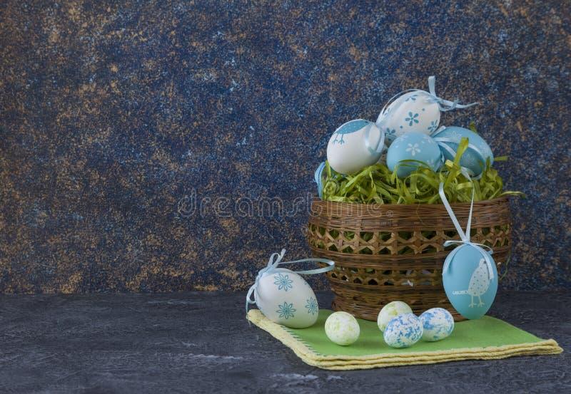 Påskbröd och blåa påskägg i en korg på mörkerstentabellen royaltyfri bild