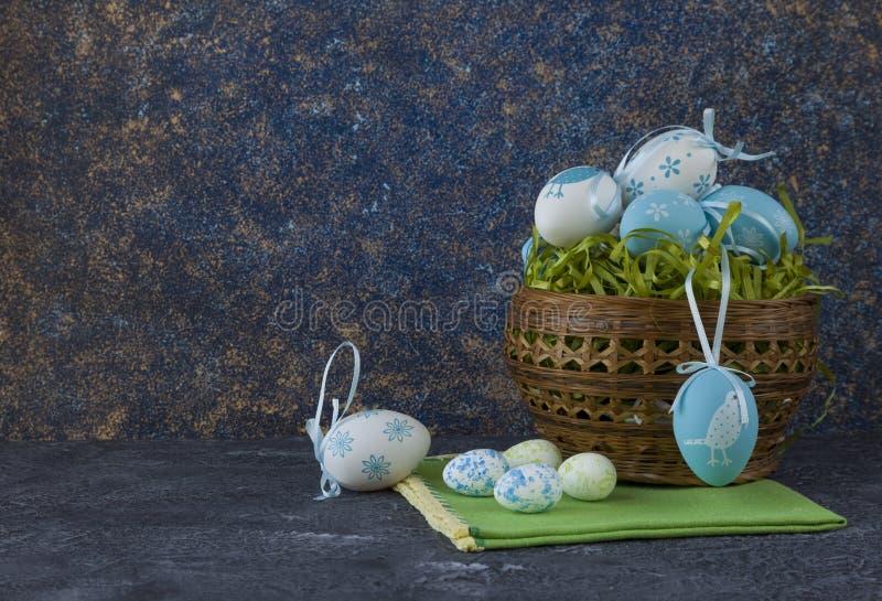 Påskbröd och blåa påskägg i en korg på mörkerstentabellen royaltyfria foton