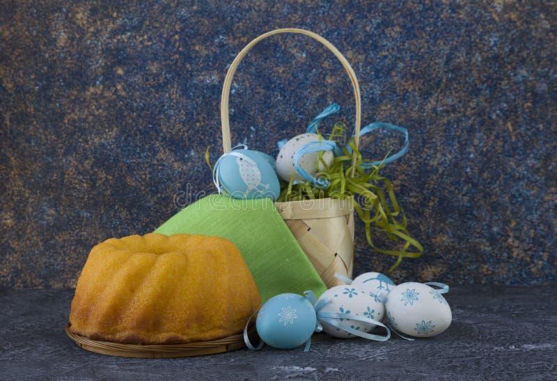Påskbröd och blåa påskägg i en korg på mörkerstentabellen fotografering för bildbyråer