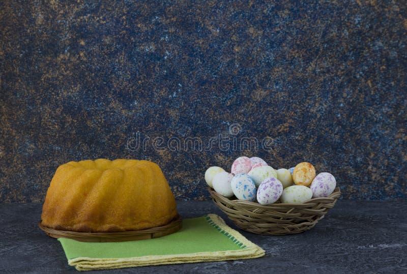 Påskbröd och mini- påskägg i en liten korg på mörkerstentabellen arkivfoton
