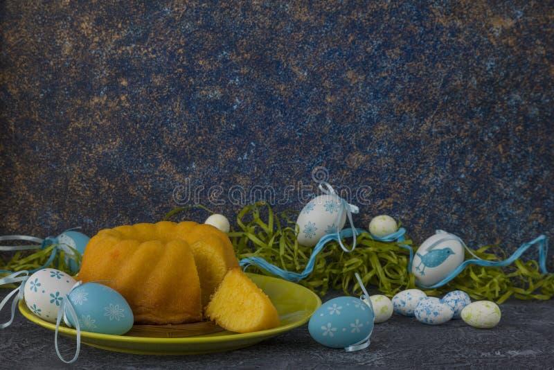 Påskbröd på den gröna plattan och målade tabellen för sten för mörker för jon för påskägg som dekoreras med grönt gräs arkivfoton