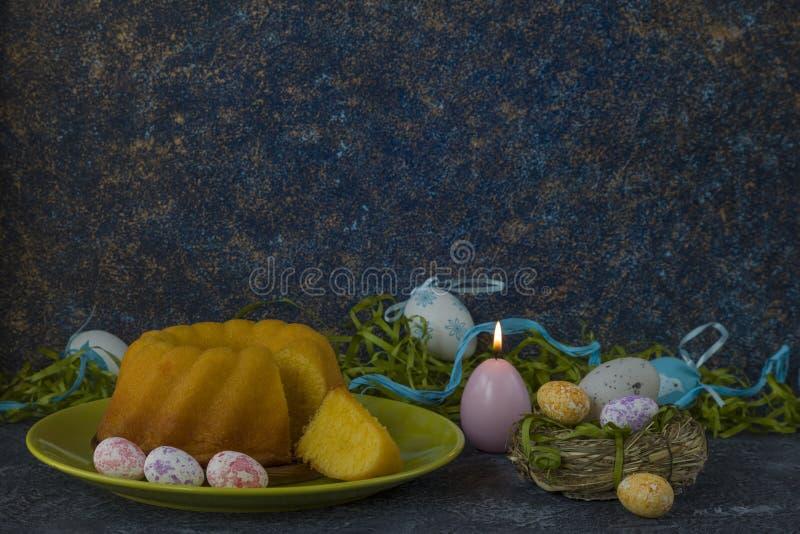 Påskbröd på den gröna plattan och målade tabellen för sten för mörker för jon för påskägg som dekoreras med grönt gräs royaltyfri foto