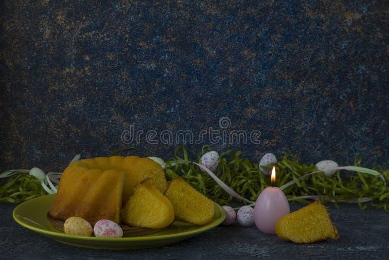Påskbröd på den gröna plattan och målade tabellen för sten för mörker för jon för påskägg som dekoreras med grönt gräs royaltyfri fotografi