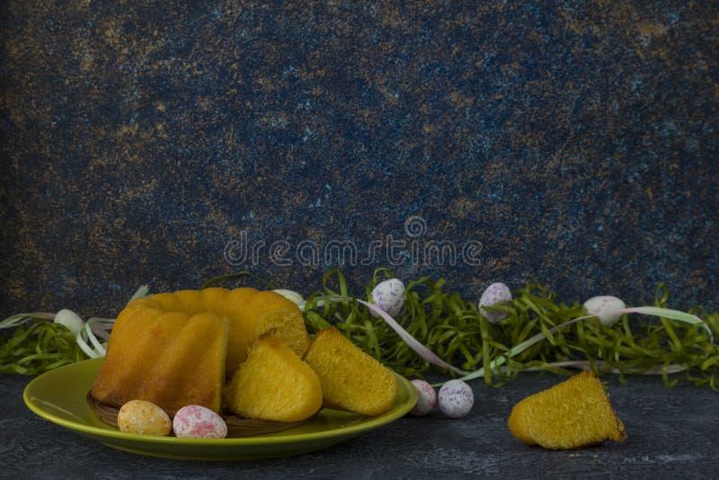 Påskbröd på den gröna plattan och målade tabellen för sten för mörker för jon för påskägg som dekoreras med grönt gräs arkivbild
