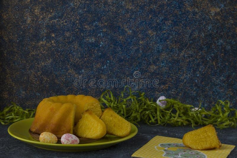 Påskbröd på den gröna plattan och målade tabellen för sten för mörker för jon för påskägg som dekoreras med grönt gräs royaltyfria bilder