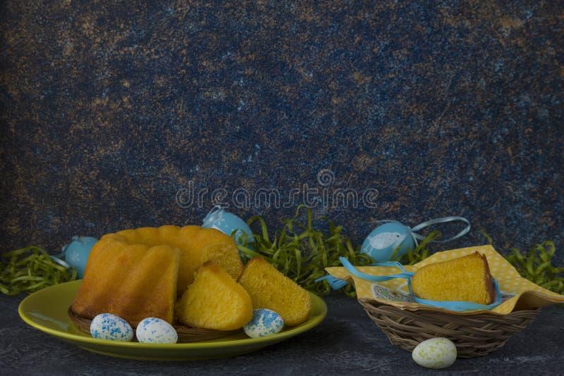 Påskbröd på den gröna plattan och målade tabellen för sten för mörker för jon för påskägg som dekoreras med grönt gräs arkivfoto