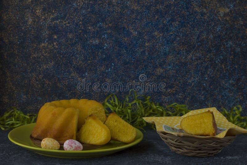 Påskbröd på den gröna plattan och målade tabellen för sten för mörker för jon för påskägg som dekoreras med grönt gräs royaltyfria foton