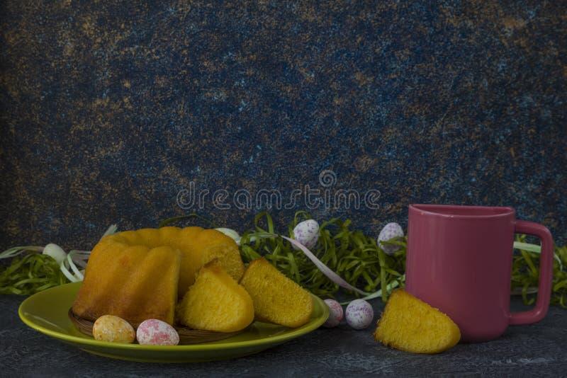 Påskbröd på den gröna plattan, rosa färg rånar och målade påskägg royaltyfria foton