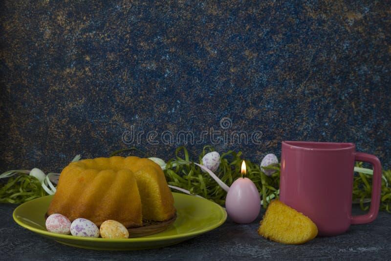 Påskbröd på den gröna plattan, rosa färg rånar och målade påskägg arkivbild