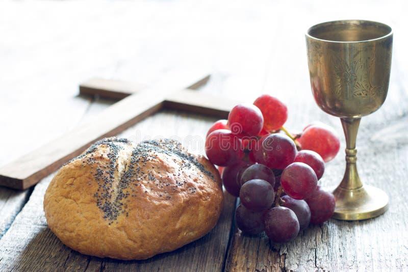 Påskbrödvin och kors på gammal träbakgrund för tappning royaltyfri foto