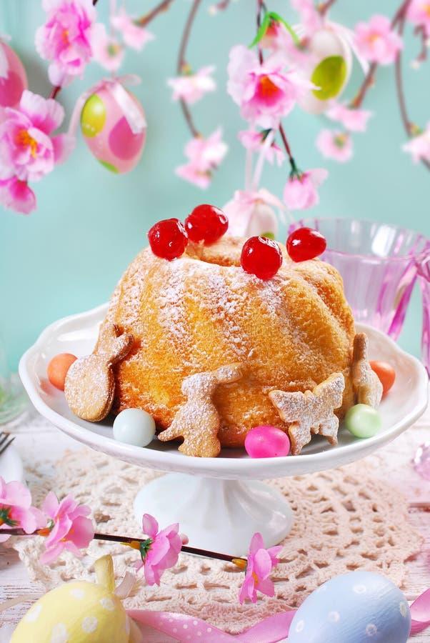 Påskcirkelkaka med körsbärsröd garnering och florsocker royaltyfria bilder