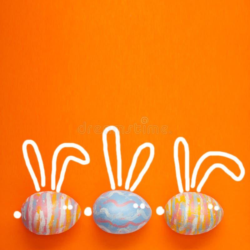 Påsken färgade ägg på en orangebackground, med målade hareöron Bakgrund för en vykort, påskbegrepp, utrymme för text arkivfoton
