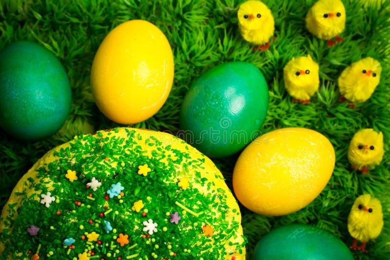 Påsken som firar kakan på grönt gräs med den gula leksaken, blir rädd royaltyfria bilder