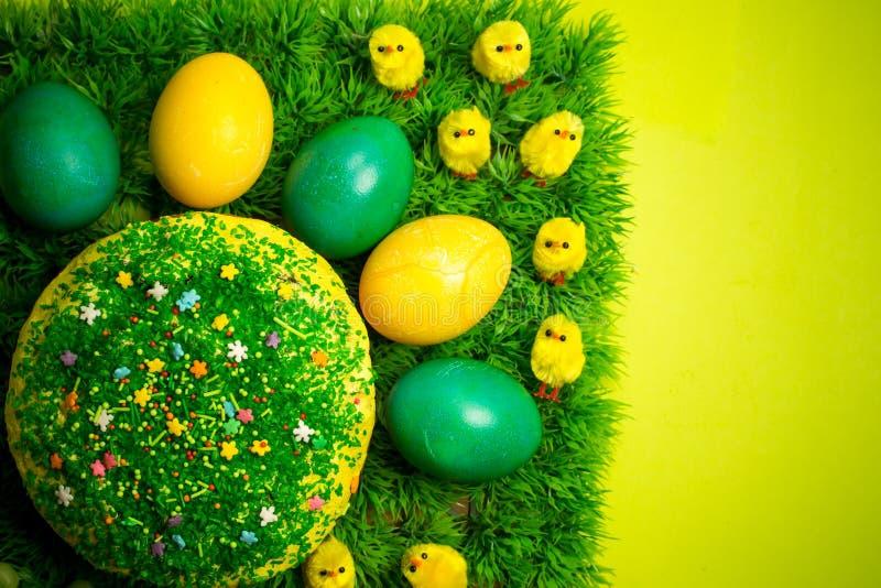 Påsken som firar kakan på grönt gräs med den gula leksaken, blir rädd royaltyfri fotografi