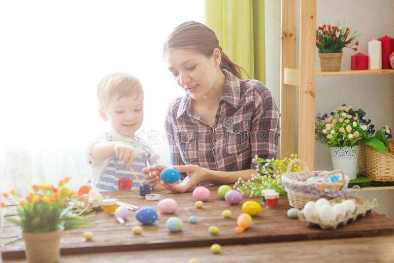 Påskförberedelser Lycklig ung moder som spenderar tid med hennes glade son Lyckliga easter för familjmamma- och barnsonmålarfärg  royaltyfri bild