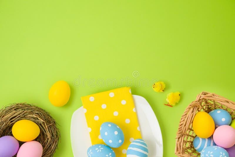 Påskferiebakgrund med easter ägg, korgen, plattan, fågelredet och fågelungegarnering royaltyfri fotografi