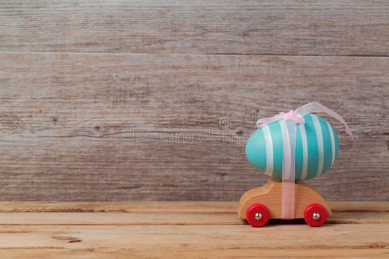 Påskferiebegrepp med ägget på leksakbilen över träbakgrund royaltyfri fotografi
