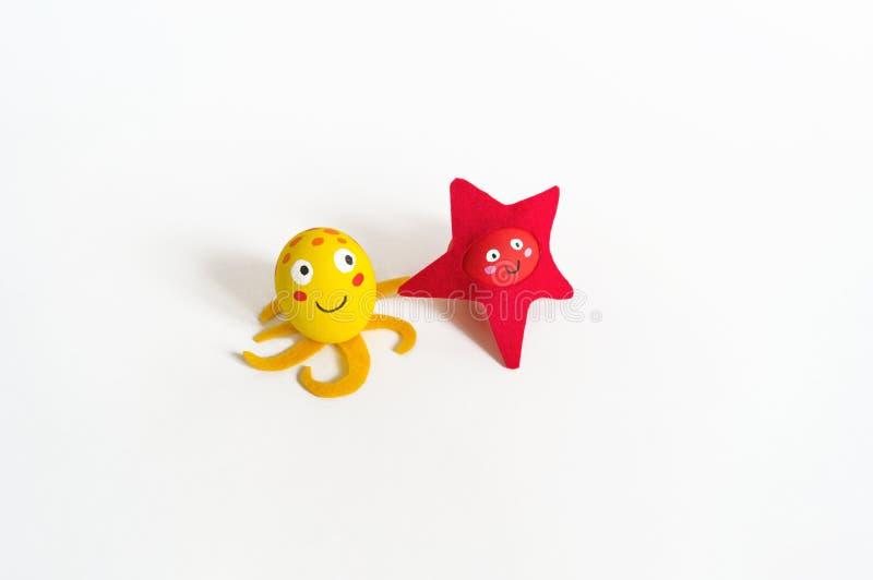 Påskferiebegrepp med gulliga handgjorda ägg: bläckfisk och sjöstjärna för havsdjur gul arkivfoton