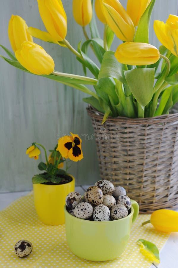 Påskferiesammansättning med gula tulpan på trätabellen arkivfoto