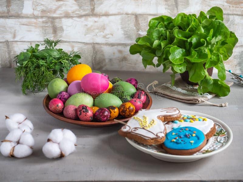 Påskfest av kulöra ägg, den målade pepparkakan, nya örter, pilris och dekorativ bomull för garnering royaltyfria foton