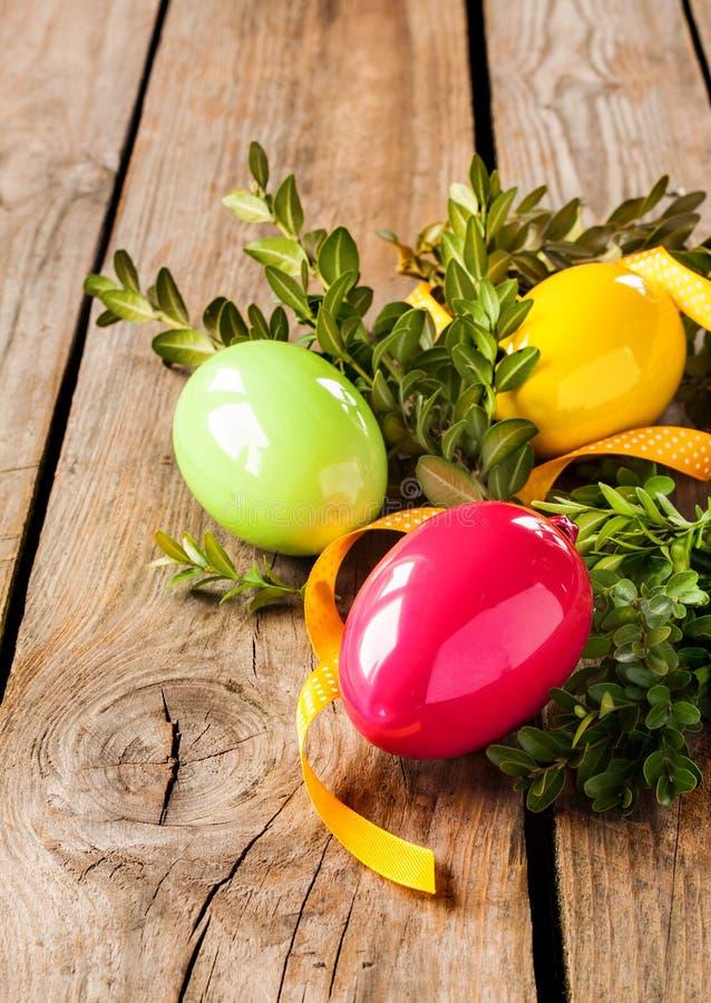 Påskgarnering - ägg med buxusen på lantligt trä arkivfoto