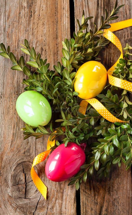 Påskgarnering - ägg med buxusen på trä royaltyfri bild