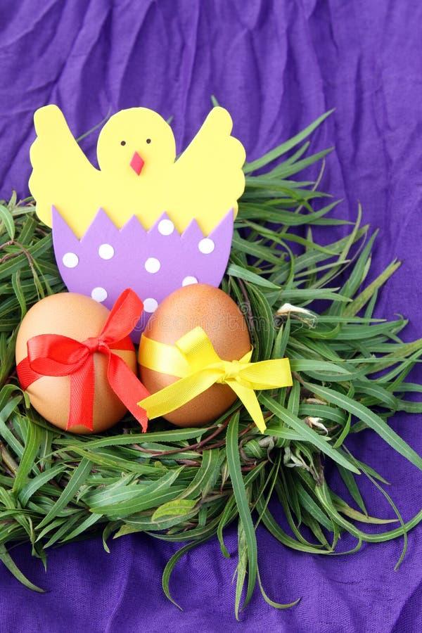 Påskgarnering: gula ägg och hand - gjord kläckt höna i äggskal i ris för grönt gräs bygga bo på purpurfärgad bakgrund arkivfoto