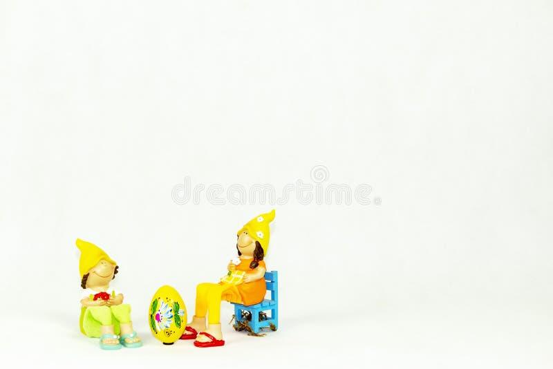 Påskgarnering med älskvärda flicka- och pojkestatyetter royaltyfria bilder