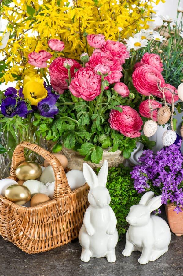 Påskgarnering med blommor, ägg, kaniner och kakan royaltyfria foton