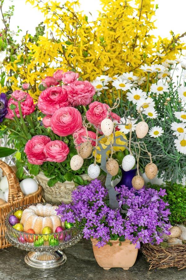 Påskgarnering med blommor, ägg och kakan royaltyfri bild