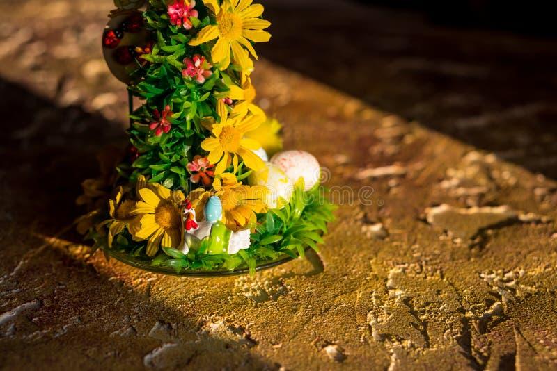Påskgarnering med fågelungar, ägg och blommor lyckligt easter ägg på tappninggulingträbakgrund lycklig ferie royaltyfri bild