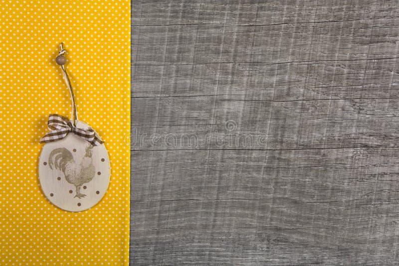 Påskgarnering med haneetiketten som hänger på en guling, prack fab arkivbilder