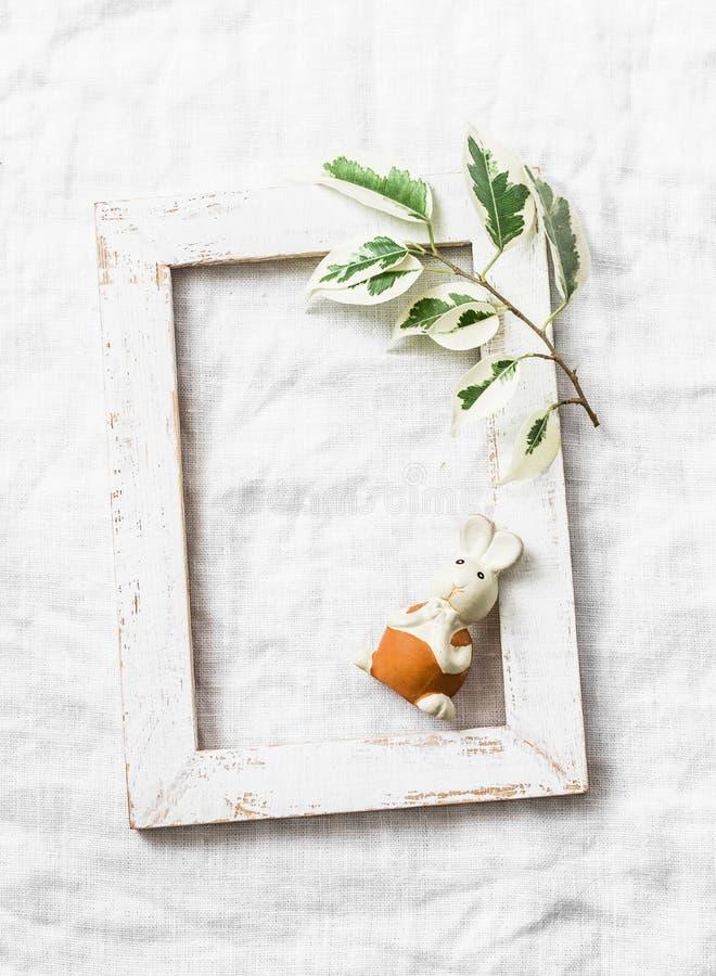 Påskgarnering - trätom ram med en kvist av gräsplansidor och den easter kaninen på en ljus bakgrund royaltyfria foton