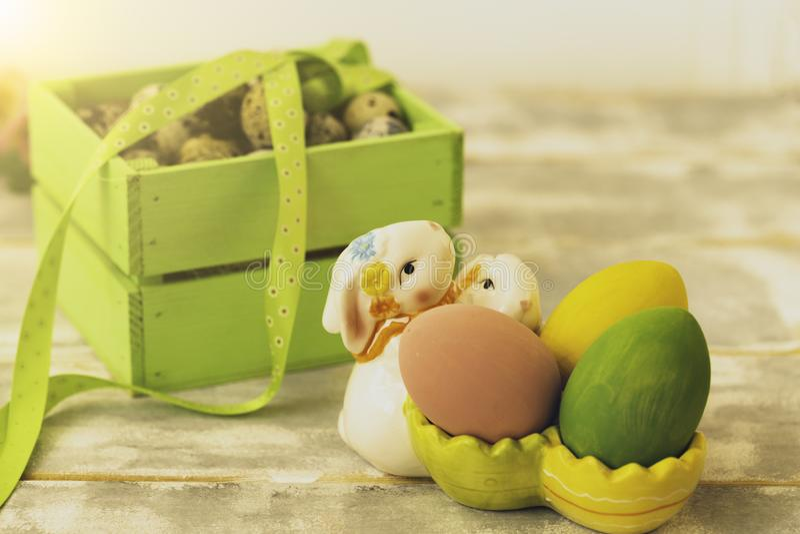 Påskgarneringar med påskägg, keramiska kaniner och band royaltyfri foto