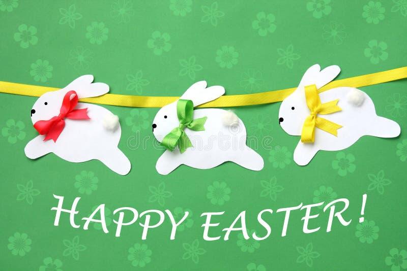 Påskhand - gjort hälsningkort: festlig pappers- kaningirland som isoleras på blommabakgrund arkivfoton