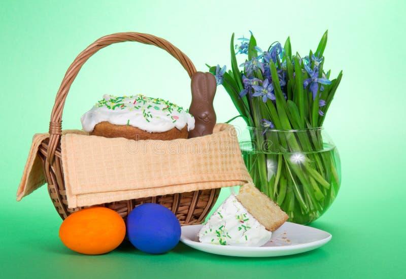 Påskkaka i korg och färgglade ägg royaltyfri fotografi