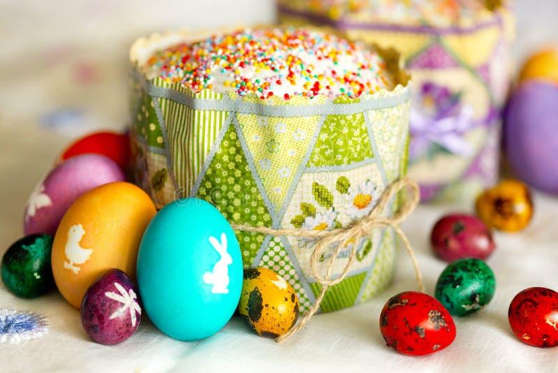 Påskkaka med sockerglasyr och färgrika - guling, rött, violett som är grön, violet - påskägg med vita bilder royaltyfri bild