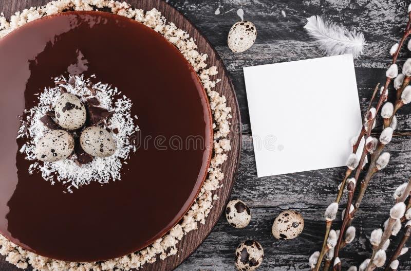 Påskkaka med spegelglasyrchoklad, kokosnöten, vårblommor, vaktelägg och anmärkningen för papperskort på lantlig bakgrund lyckliga arkivfoton