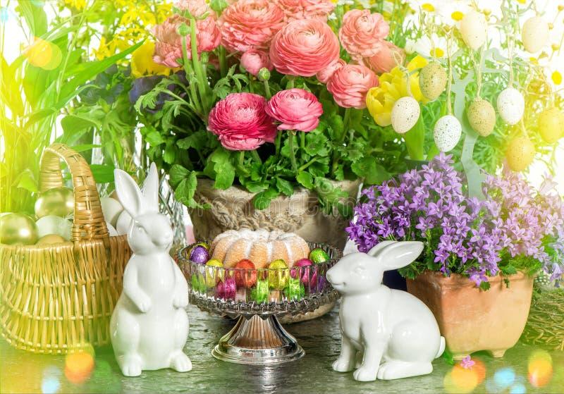 Påskkaka, vårblommor, ägg och kanin Ljusläckor royaltyfria foton