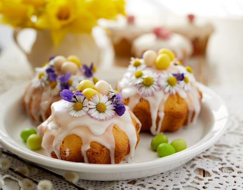 Påskkakor som täckas med isläggning som dekoreras med våren och ätliga blommor och marsipanägg på en påsktabell royaltyfri fotografi